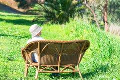 妇女坐一条长凳在庭院里 免版税库存图片