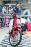 妇女坐一辆摩托车在商店 免版税图库摄影