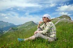 妇女坐与三叶草花的一座山 图库摄影