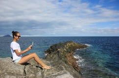 妇女坐与地图的岩石岸 免版税图库摄影