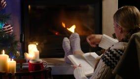 妇女坐与杯子热的饮料和书在壁炉附近 影视素材