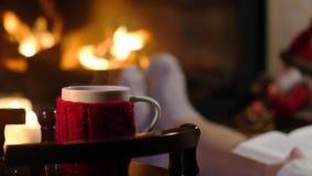 妇女坐与杯子热的饮料和书在壁炉附近 股票录像
