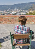 妇女坐与格拉茨都市风景的公园长椅,奥地利 免版税库存图片