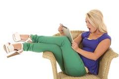 妇女坐与片剂震惊的绿色裤子 免版税库存照片