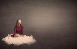 妇女坐与简单的bakcground的一朵云彩 库存图片
