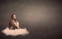 妇女坐与简单的bakcground的一朵云彩 库存照片