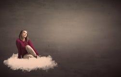 妇女坐与简单的bakcground的一朵云彩 免版税图库摄影
