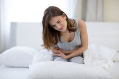 妇女坐充满痛苦的床