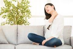 妇女坐充满脖子痛的沙发 图库摄影