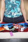 妇女坐加有厚软垫的手提箱 免版税库存照片