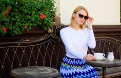 妇女坐单独defocused咖啡馆大阳台都市的背景 怎么喜欢是唯一技巧 妇女偏僻的等待日期 约会 免版税库存照片