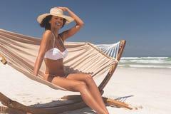 妇女坐吊床在海滩在一好日子 库存照片