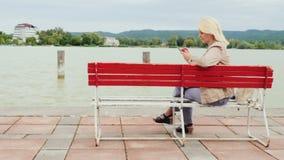 妇女坐在一个大湖的背景的一条长凳 使用一个手机 balaton匈牙利湖 股票录像