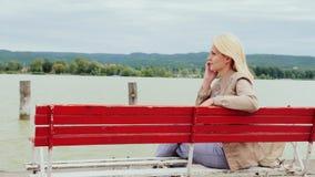 妇女坐在一个大湖的背景的一条长凳 在电话里说 balaton匈牙利湖 影视素材