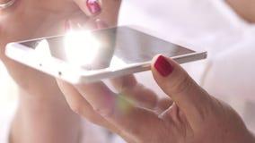 妇女坐在与智能手机的一个窗口 妇女输入查寻箱子在智能手机的文本 2th混淆女孩岁月 影视素材