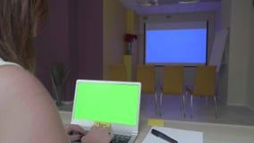 妇女坐在与膝上型计算机的桌上有在蓝色放映机屏幕,类型前面的绿色屏幕的,并且纸卷筛选,当时 股票录像