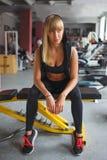 妇女坐在健身房的一条长凳 库存照片