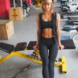 妇女坐在健身房的一条长凳 库存图片