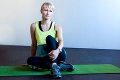 妇女坐在健身房的席子 免版税库存照片