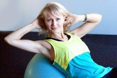 妇女坐在健身房的球 免版税库存照片