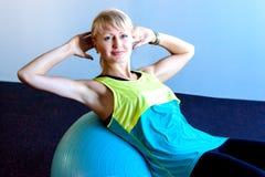 妇女坐在健身房的球 免版税库存图片