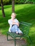 妇女坐在公园垂直的长凳 库存图片