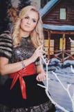 妇女坐在冬天天气的一条长凳 免版税库存照片