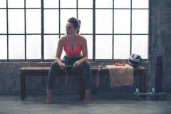 妇女坐在听到在设备的音乐的顶楼健身房的长凳 库存图片