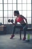 妇女坐在外形举的重量的长凳在顶楼健身房 免版税图库摄影