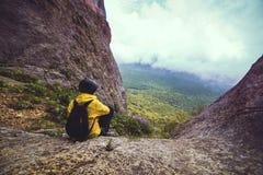 妇女坐在岩石的adge 免版税库存照片