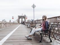 妇女坐在布鲁克林大桥和looki的一条长凳 库存照片