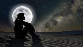 妇女坐在月光的沙子 免版税图库摄影