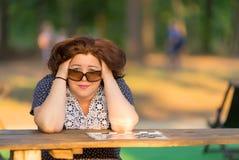 妇女坐在桌上在公园 图库摄影