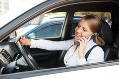 妇女坐在汽车和联系在电话 免版税图库摄影