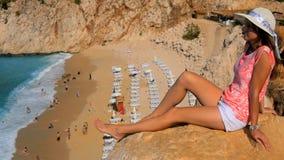 妇女坐在沙子海滩上的峭壁 股票录像