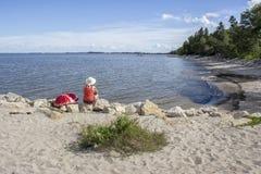 妇女坐在注视横跨湖的海滩的一个岩石 图库摄影