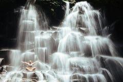 妇女坐在瑜伽姿势的岩石在小瀑布瀑布下 免版税库存图片