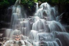 妇女坐在瑜伽姿势的岩石在小瀑布瀑布下 库存图片