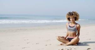 妇女坐在莲花姿势的海滩 免版税库存照片