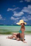 妇女坐在黄色帽子的海滩 库存图片