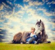 妇女坐在说谎的马和看外面在牧场地背景 免版税库存图片