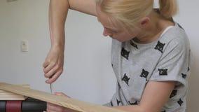 妇女坐地板在屋子里收集木家具,扭转有螺丝刀的螺丝 股票录像