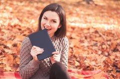 妇女坐地毯和尖酸的书 免版税库存照片