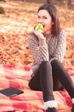 妇女坐地毯和尖酸的苹果 库存图片