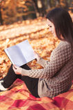 妇女坐地毯和阅读书 免版税库存图片