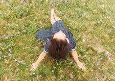 妇女坐夏天草甸 免版税库存照片