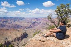 妇女坐大峡谷的外缘 免版税库存图片