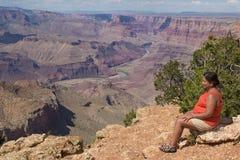 妇女坐大峡谷的外缘 免版税库存照片