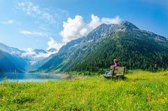 妇女坐天蓝色的山湖奥地利长凳  免版税库存图片