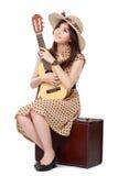 妇女坐她的手提箱,当弹吉他时 免版税库存图片